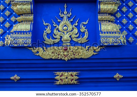 Traditional Thai style pattern decorative, stucco gold paint on a blue indented background in Buddhist temple Chiang Rai,Thailand. - stock photo