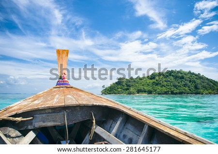 Traditional Thai wooden longtail boat heads toward the tropical Andaman shores of Bamboo Island, a popular day trip from Koh Phi Phi - stock photo