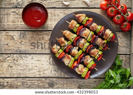Traditional turkey or chicken meat skewers shish kebab with onion and tomatoes, parsley, ketchup in clay dish on rustic wooden table background. Barbecue grill food. - stock photo