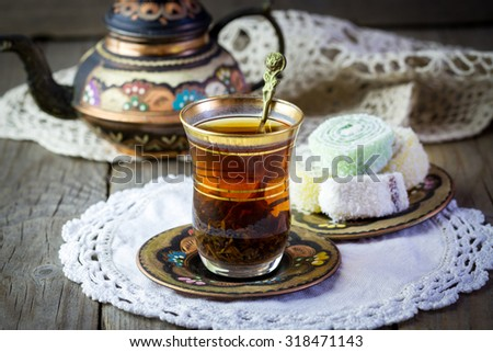 Traditional Turkish tea set: glass cup of tea, painted copper teapot, Turkish delight on a plate and vintage napkin on old wooden table - stock photo