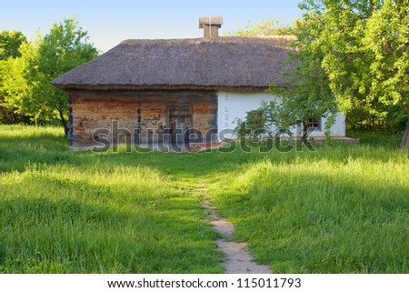 Traditional ukrainian rural house with a straw roof - stock photo