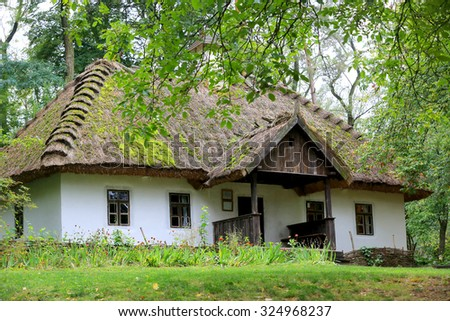 Traditional Ukrainian rural house with reeds roof in green forest - stock photo