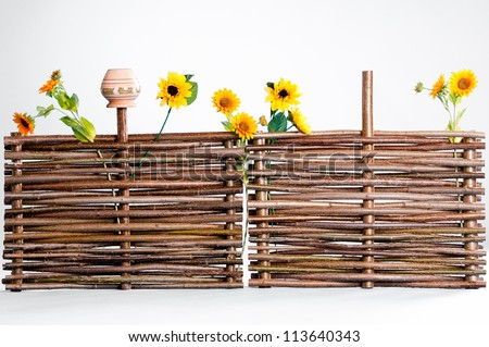 Traditional ukrainian wattle with sunflowers and pot - stock photo
