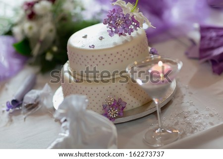 Traditional wedding cake with purple flowers - stock photo