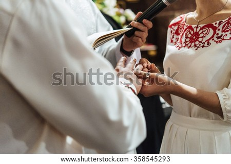 traditional wedding ceremony of stylish elegant  bride and groom in the old church, putting on ring moment - stock photo