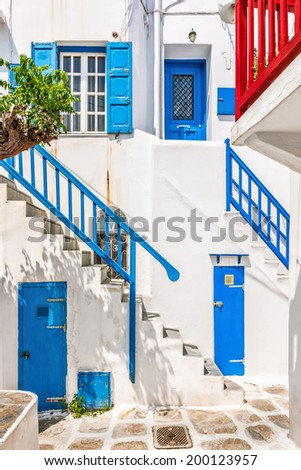 Traditional white houses with blue railing, doors and shutters in Mykonos, Cyclades, Greece - stock photo
