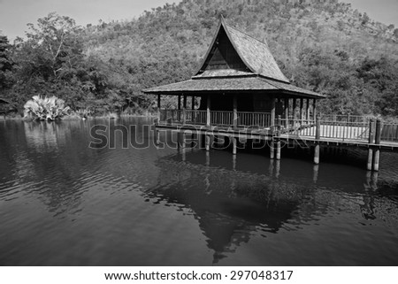 Traditional wood Thai house above the lake with mountain - stock photo