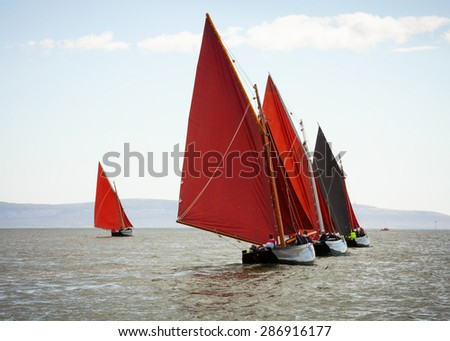 Traditional wooden boats Galway Hooker, with red sail, compete in regatta. Ireland. - stock photo