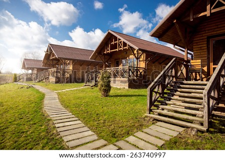 Traditional wooden cottages at sunny day in the countryside - stock photo