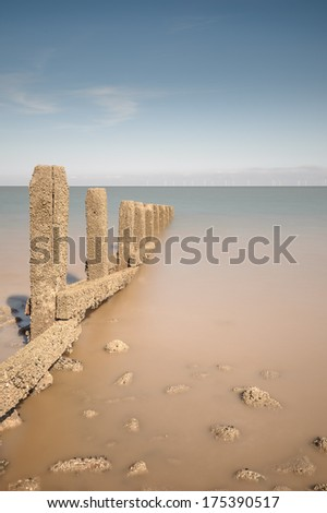 Traditional wooden groynes reach out into the sea off Llanddulas beach in North Wales. The North Hoyle offshore wind farm is on the horizon. - stock photo
