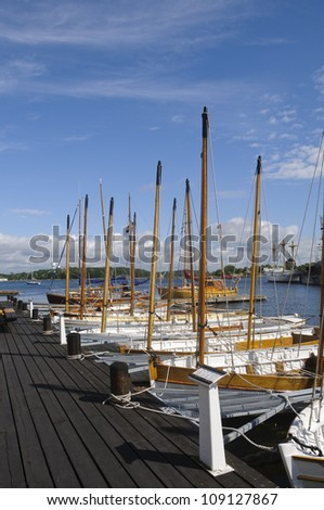 Traditional wooden sloops moored at the pier of Karlskrona marina, Sweden - stock photo