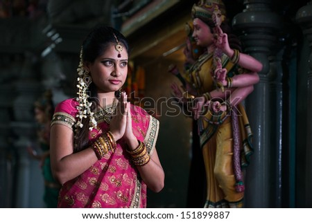 traditional Young indian girl praying in the temple  - stock photo