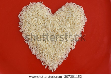 Traditionally Indian basmati Rice in heart shape in a red plate, isolated over white with copy space.Symbol of love or LUV White rice or biriyani rice Kerala India - stock photo