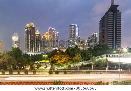 Traffic captured with long exposure along one of the city main avenue in the Central Business District after sunset in Jakarta in Indonesia capital city. - stock photo