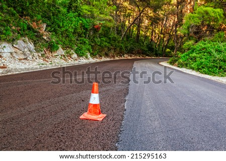 Traffic cone on a newly paved road through the forest - stock photo