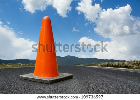 traffic cone on a road with copy space - stock photo