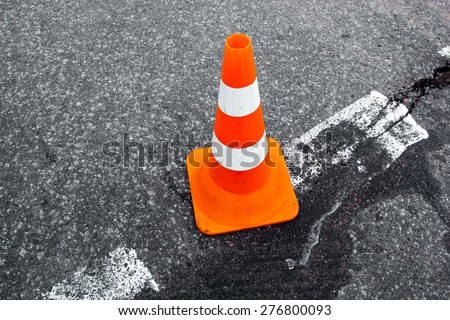 Traffic cone on the asphalt surface with partly rubbed out white road marking line. Close up. - stock photo