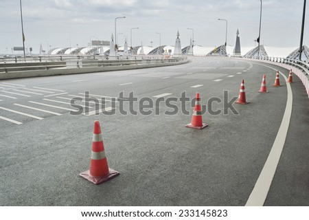 Traffic cone placed on the curving road in Bangkok, Thailand - stock photo