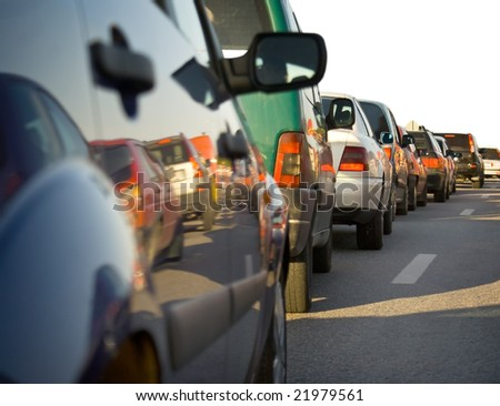 Traffic congestion - a long queue of cars, with reflection of some of the cars in the next lane. Partly isolated on white. - stock photo
