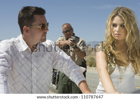 Traffic cop aiming gun at couple on street - stock photo