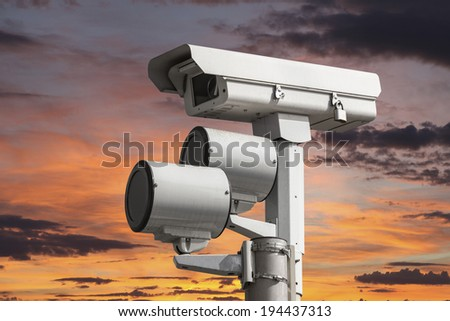 Traffic intersection signal surveillance camera with sunset sky. - stock photo