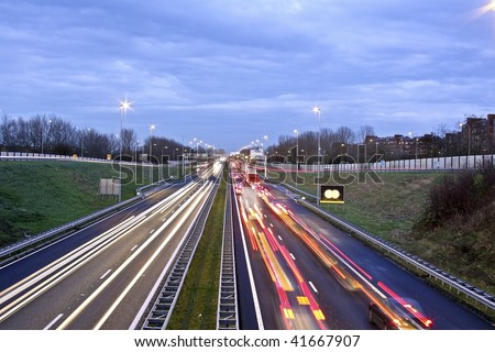 Traffic jam on the famous highway A9 near Amsterdam in the Netherlands at twilight - stock photo