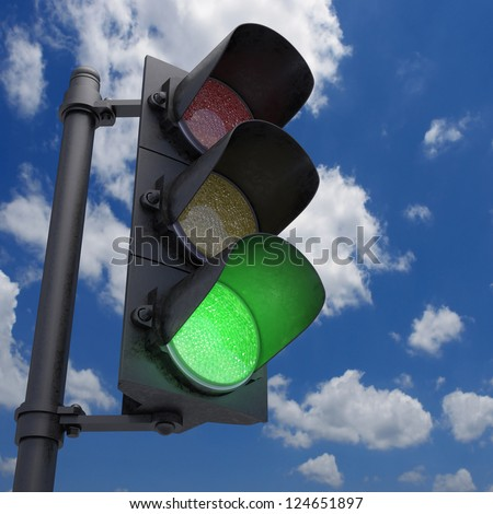 Traffic Light in a blue sky with only the green light on. - stock photo