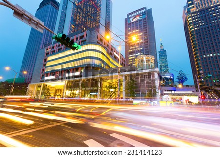 traffic light trails in modern street of Taipei.The chinese words are the road name and traffic signs. - stock photo
