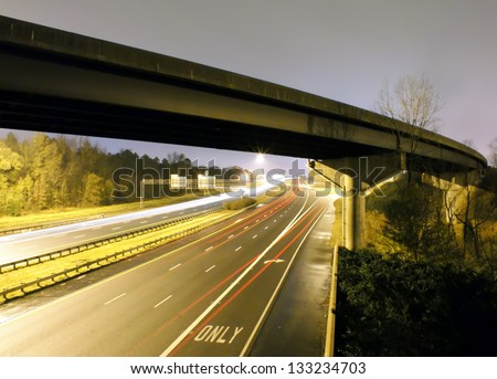 traffic light trails under bridge - stock photo