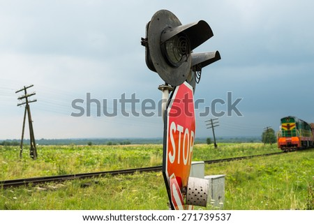 Traffic lights and signs at the railroad crossing and the approaching train (Ukraine). - stock photo
