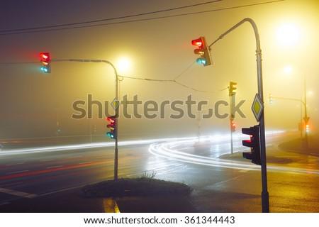 Traffic lights - crossroad in the foggy night - stock photo