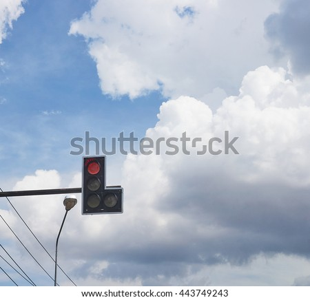 Traffic lights with red light near street lamp and electrical cable; beautiful blue sky and rain cloud background as a copy space. - stock photo