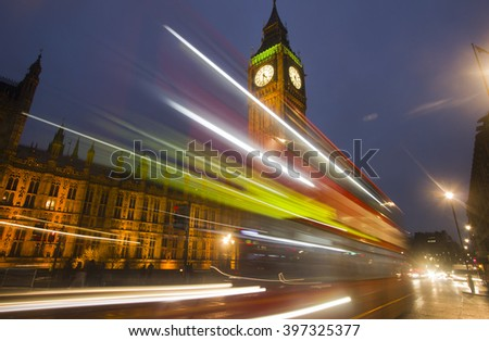 Traffic of cars and busses drives by Big Ben at Westminster Parliament in London in the evening - stock photo