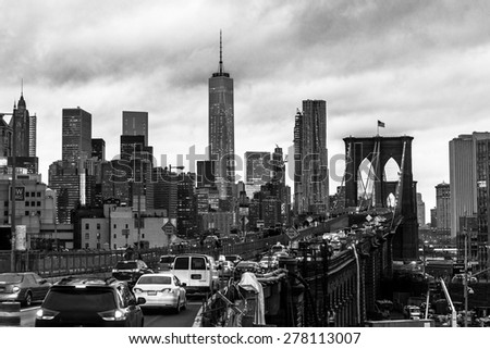 Traffic on Brooklyn bridge and New York City Manhattan downtown skyline at dusk with skyscrapers over East River panorama. Black and white. - stock photo