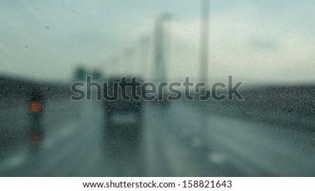 Traffic rain (focused on small rain drops on glass) - stock photo
