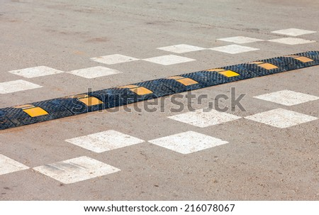 Traffic safety speed bump on an asphalt road - stock photo