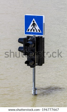 Traffic sign and pedestrian crossing sign in flood  - stock photo
