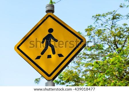 Traffic sign pedestrian crossing road - stock photo