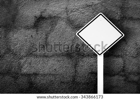 traffic sign post with dark crack wall background - stock photo