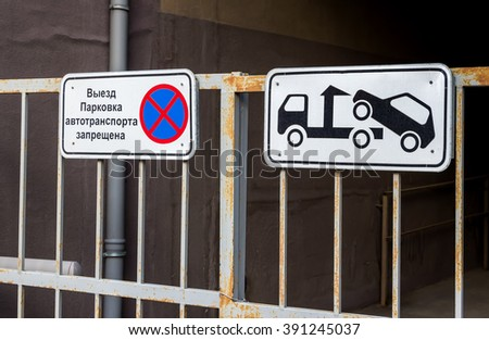 """Traffic sign prohibiting parking mounted on metal gate. Evacuation on tow truck. Text in Russian: """"Parking of vehicles is prohibited"""" - stock photo"""