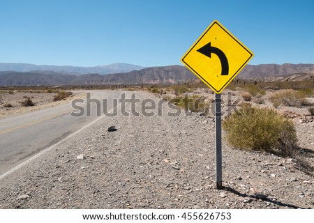 Traffic sign warning of a bend in the Argentinian Andes - stock photo