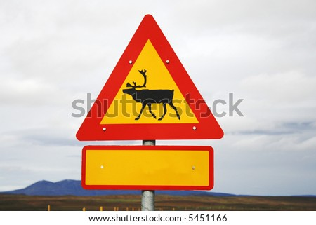 Traffic sign with reindeer next to deserted road. With blank notice to use for your own text for christmas - stock photo