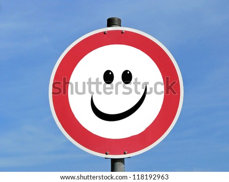 Traffic sign with smiling face, against blue sky - stock photo