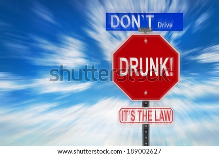Traffic signs against a cloudy blue sky with the words Don't Drive Drunk, it'??s the Law written on them.  Image is blurred to imply motion and blurred vision due to intoxication.      - stock photo