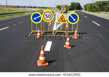 traffic signs during repair and paint work on the fenced road cones - stock photo