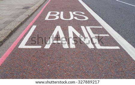 Traffic signs indicating lane reserved to buses and public transport means on a London street - stock photo