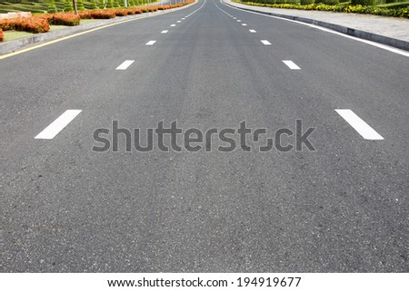 Traffic symbol on surface road with red flowers. - stock photo