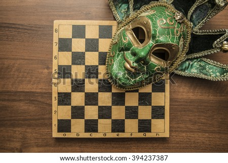 Tragicomic venice carnival Masks. Green luxury masks over chessboard background lie on wooden table - stock photo