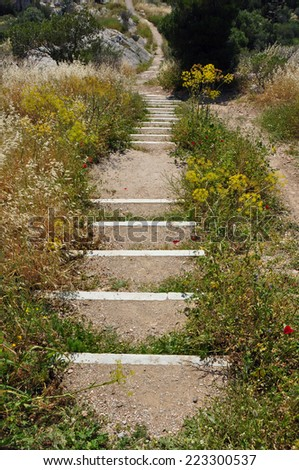 Trail footpath with crooked steps on hill slope. - stock photo