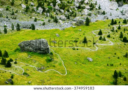 trail in the Alps, beautiful mountain landscape with a winding path - stock photo